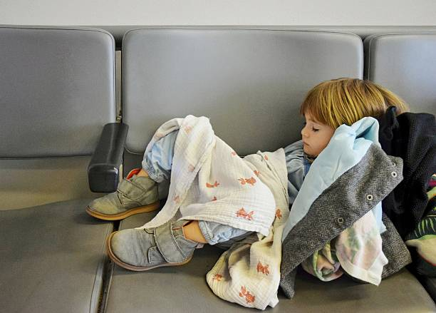 Sleepy traveler Little girl naps in an airport terminal jet lag stock pictures, royalty-free photos & images