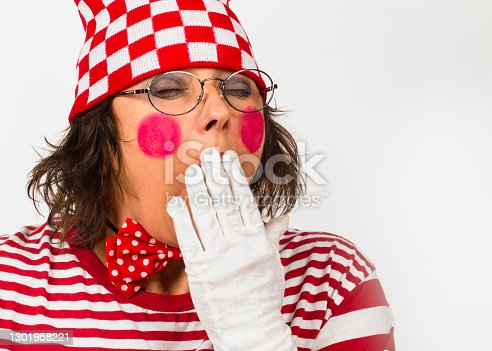 Clown bored yawning tired covering mouth with hand on a white background, copy space. Elderly female mime feeling exhausted, sleepy, tired, overworked, no energy headshot.