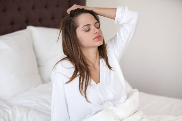 Sleepy woman feeling hangover headache after waking up in bed Sleepy young woman feeling drowsy or dizzy after waking up in bed, suffering from lack of sleep deprivation, insomnia, morning headache or migraine, having hangover after sleepless night concept aftereffect stock pictures, royalty-free photos & images