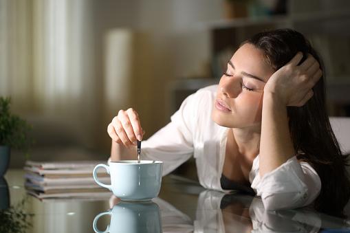 Sleepy woman stirring coffee in the morning