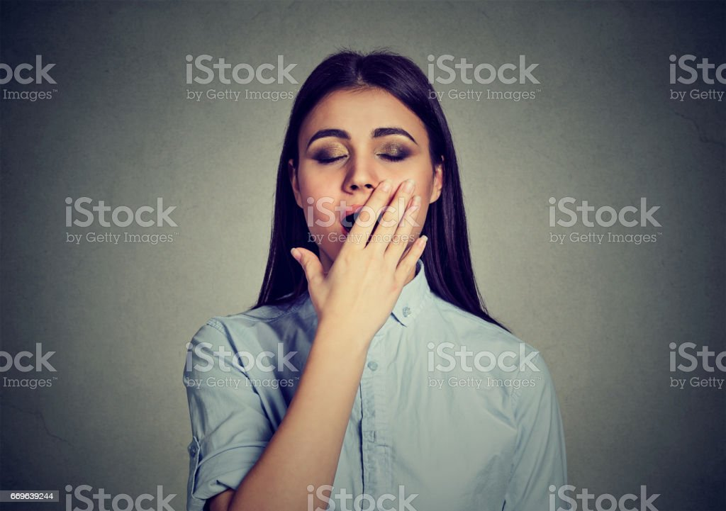 Sleepy woman with wide open mouth yawning eyes closed covering mouth with hand stock photo