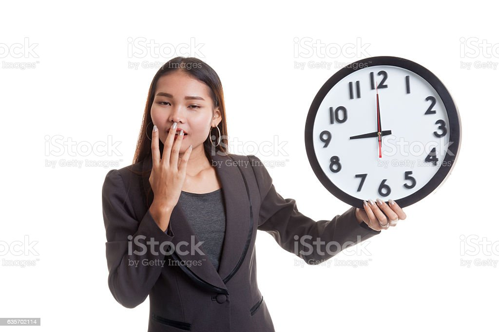 Sleepy young Asian business woman with a clock in the royalty-free stock photo