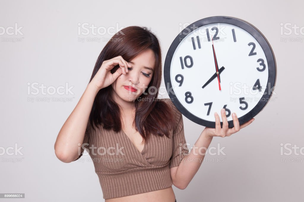 Sleepy young Asian woman with a clock in the morning. stock photo