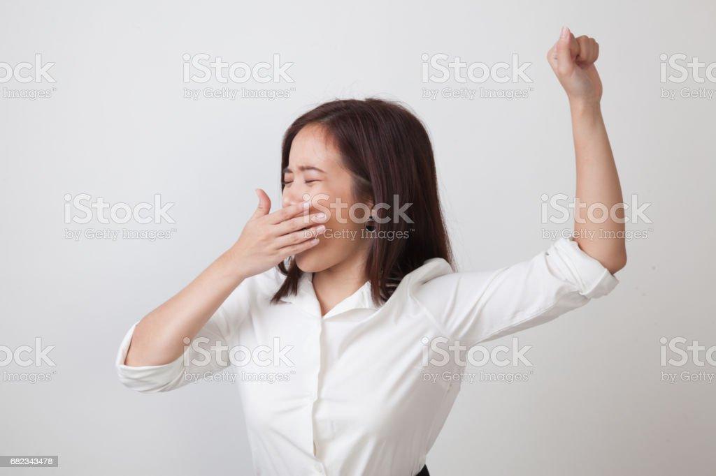 Sömnig ung asiatisk kvinna gäspning. royaltyfri bildbanksbilder