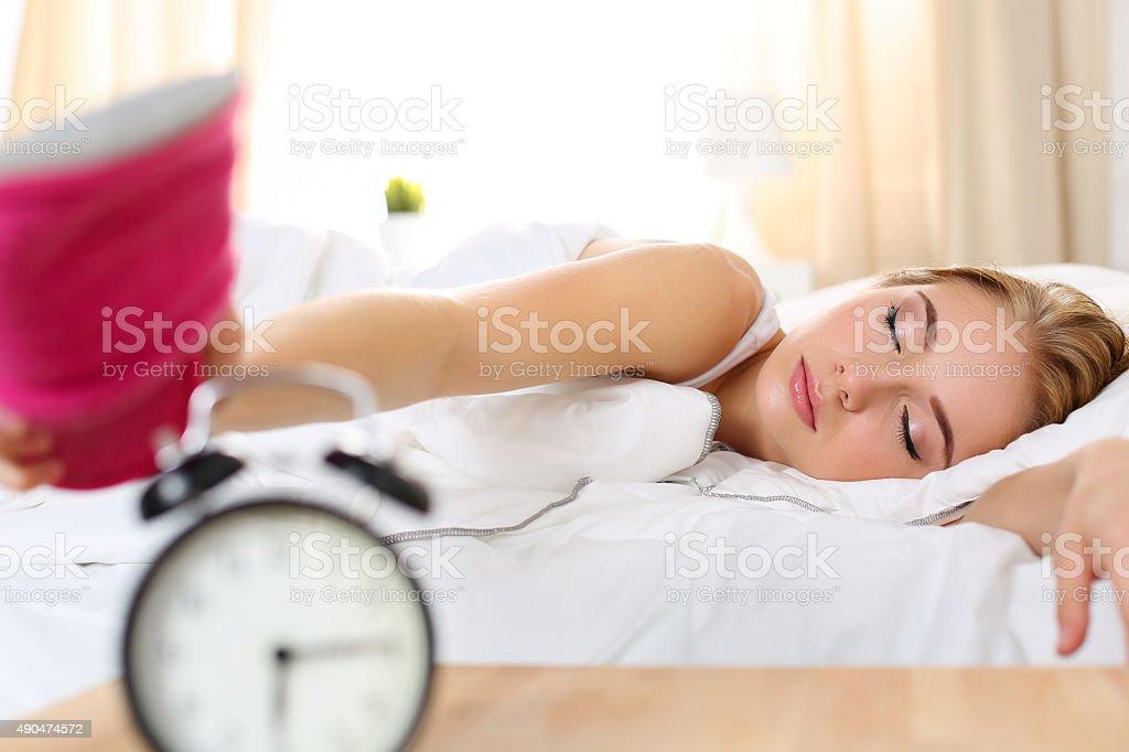 Sleepy young beautiful woman trying kill alarm clock stock photo