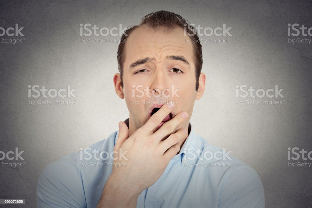 sleepy young businessman funny guy placing hand on mouth yawning stock photo