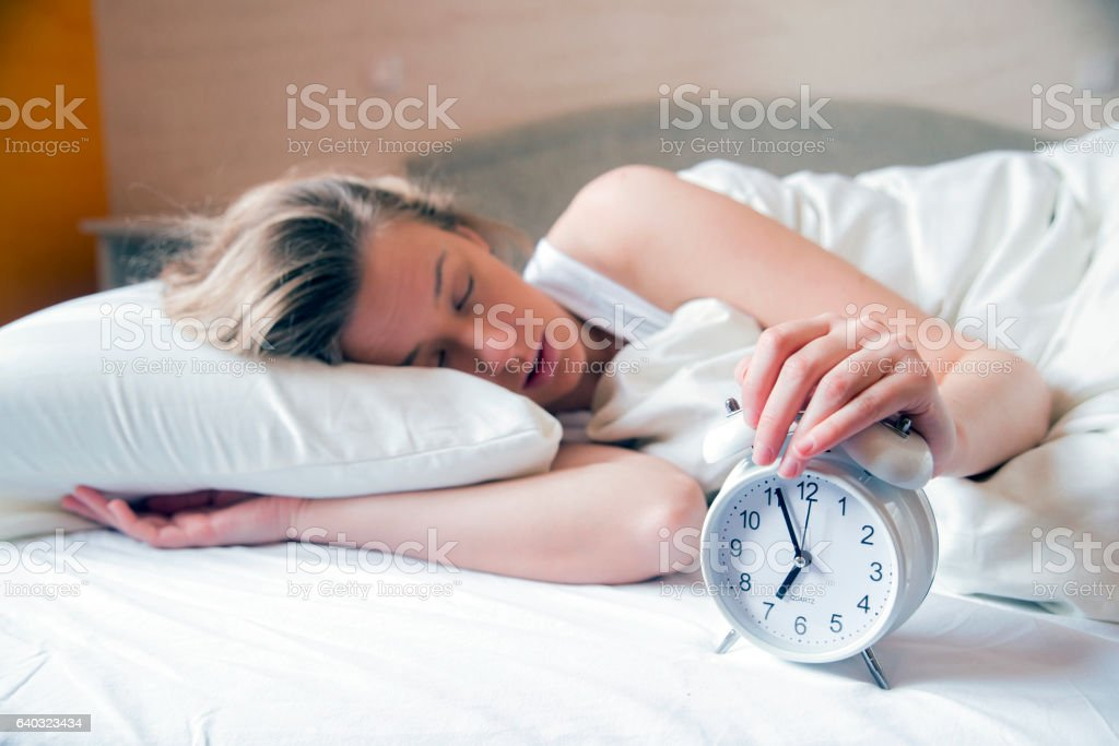 Sleepy young woman stretching hand to ringing alarm stock photo