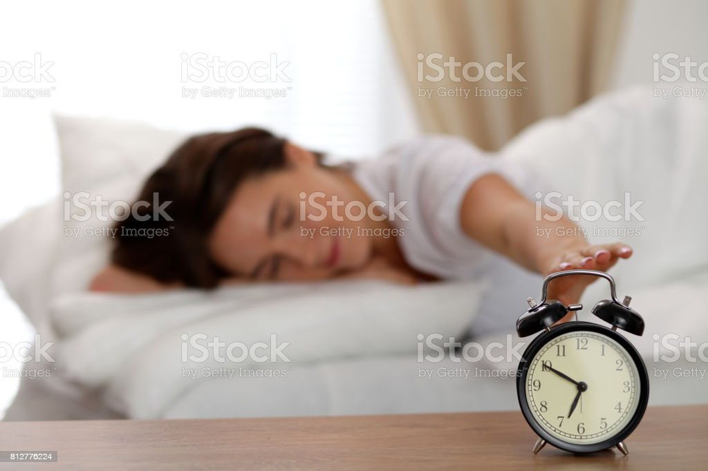 Alongamento mão de mulher jovem com sono para tocar alarme disposto desligá-lo. Cedo acordar, não dormir o suficiente, ficando o conceito de trabalho. - foto de acervo