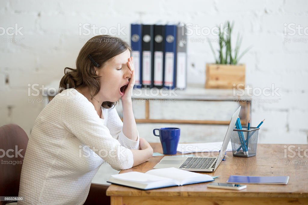 Sleepy young worker woman yawning stock photo