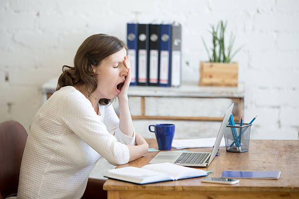 sleepy young worker woman yawning - moe stockfoto's en -beelden