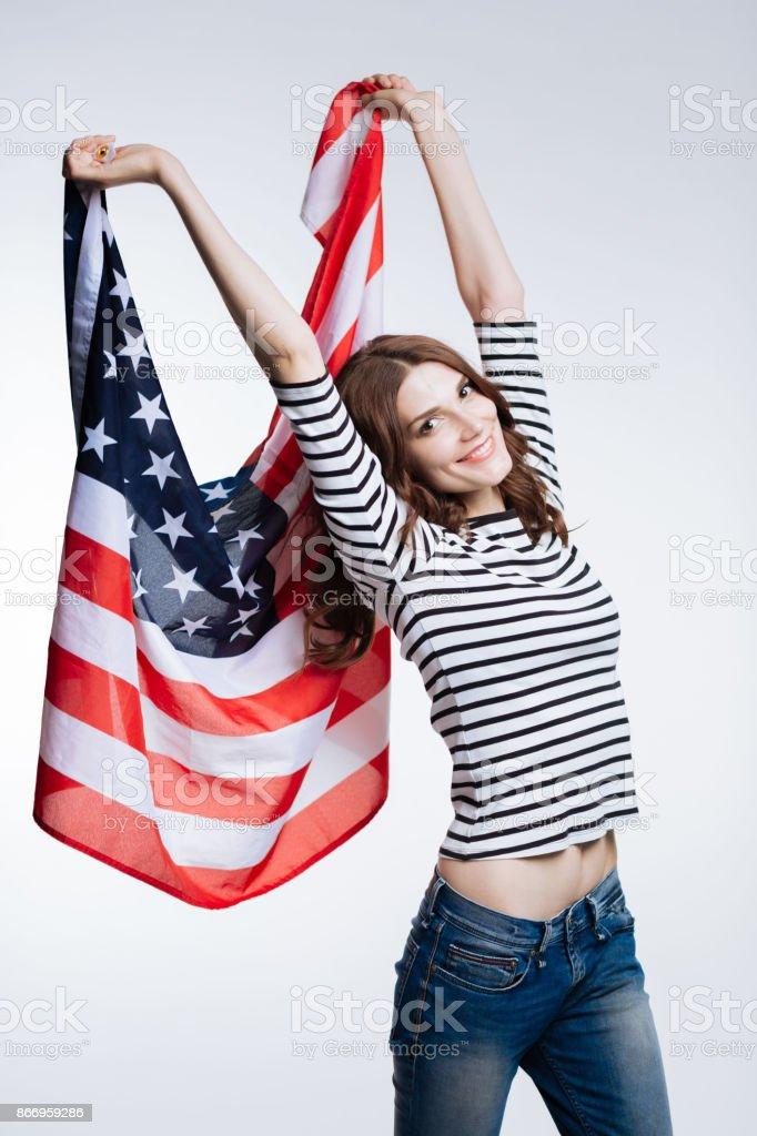 Slender auburn-haired woman lifting up US flag stock photo