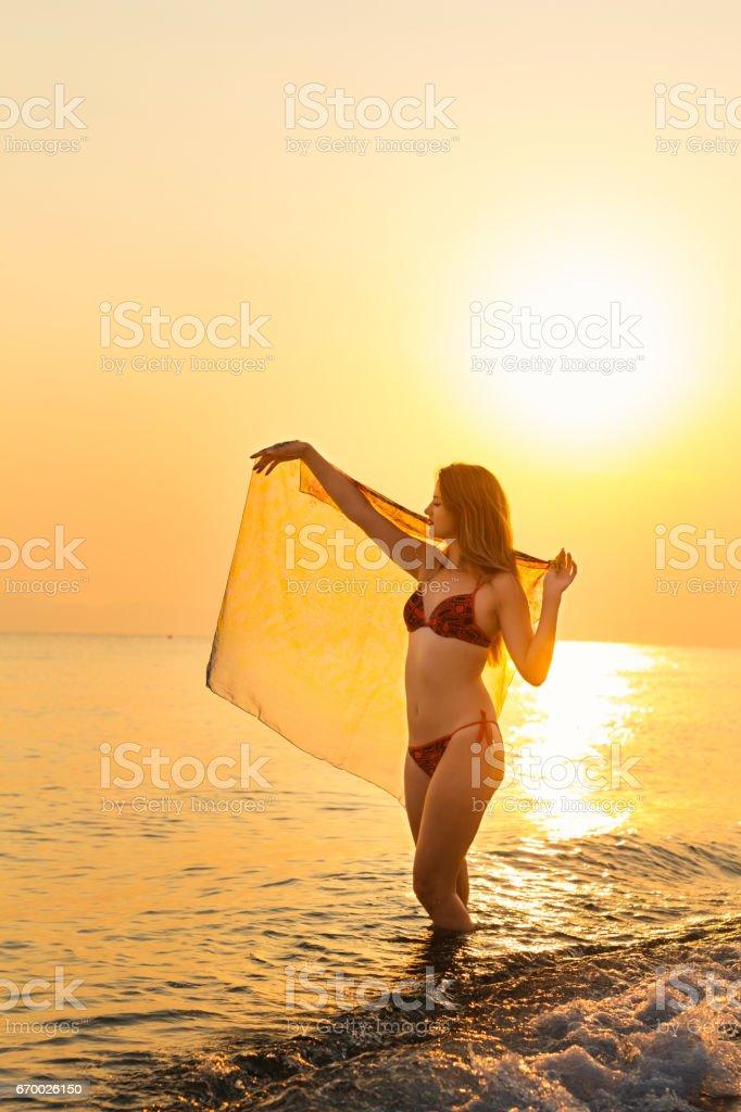 Slender beautiful woman girl on beach with pareo shawl stock photo