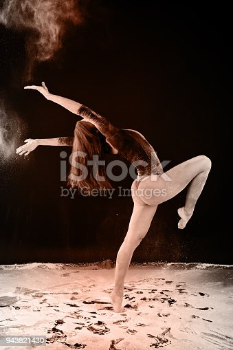 istock Slender blonde dancing in white dust studio shot 943821430