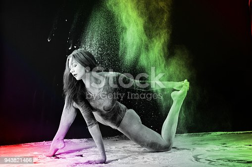 istock Slender blonde dancing in white dust studio shot 943821466