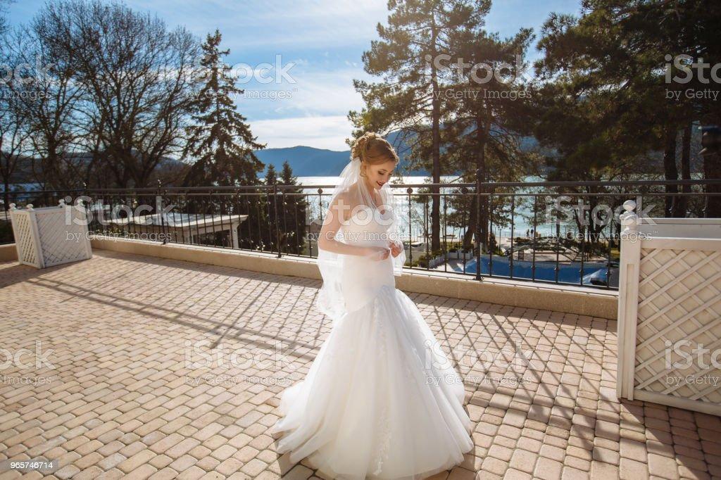 Een slanke bruid wandelingen langs de straat en geniet van de warmte van de zon en de blauwe hemel. Frisse lucht en de schoonheid van de natuur bevalt haar - Royalty-free Beschermd natuurgebied Stockfoto