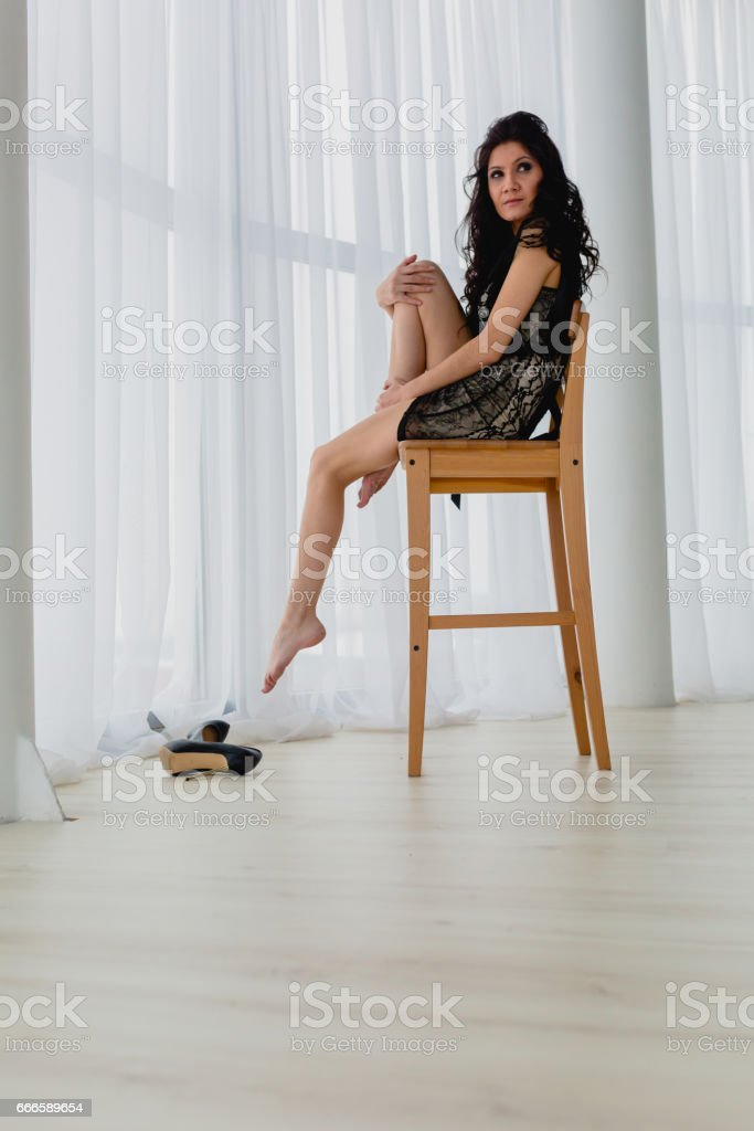 Slender brunette sitting on a wooden chair stock photo
