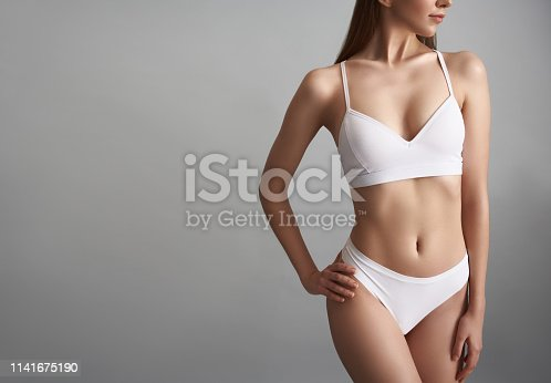 Young slim girl is standing in white underwear. Copy space in left side