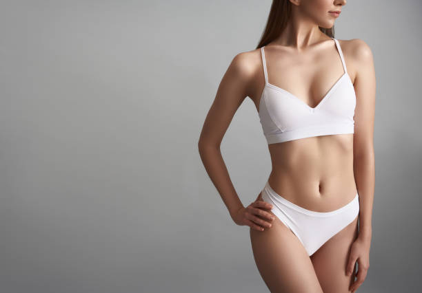 Slender female in lingerie isolated on grey background Young slim girl is standing in white underwear. Copy space in left side the human body stock pictures, royalty-free photos & images