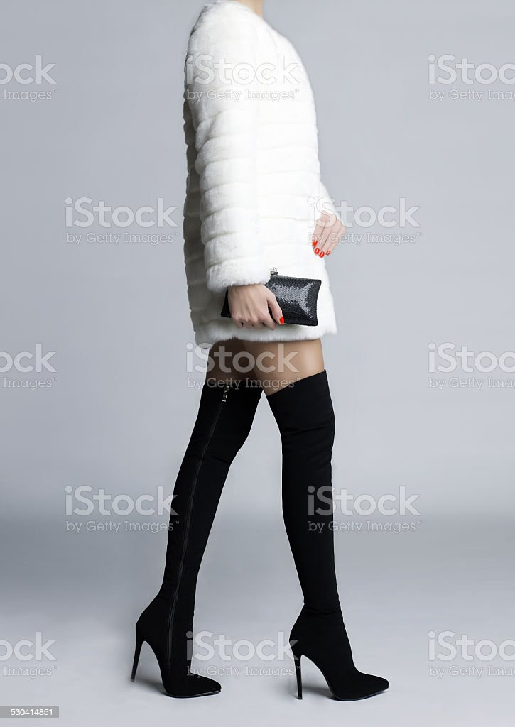 Slender female legs in boots stockings stock photo