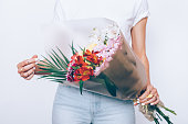 Slender girl in jeans and a T-shirt is holding a bouquet