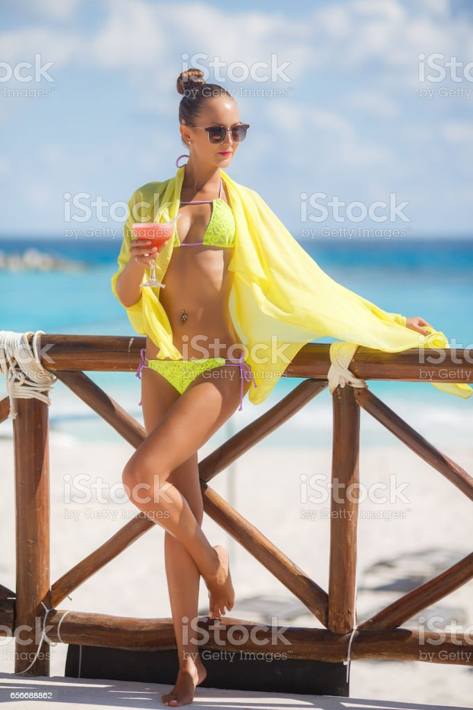 Slender girl on background of ocean with a cocktail - foto stock
