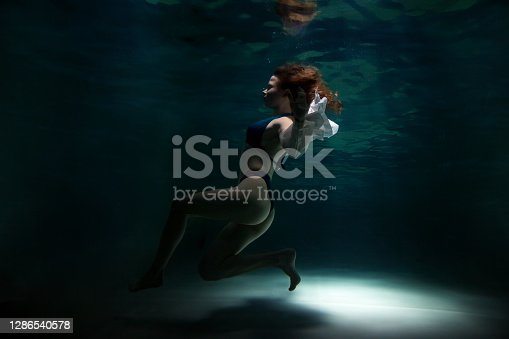 Slender pretty young woman brunette in bathing suit and white blouse in dark pond, illuminated by moonlight. Elegant female underwater. Concept of beauty, tenderness and striving for ideal. Copy space