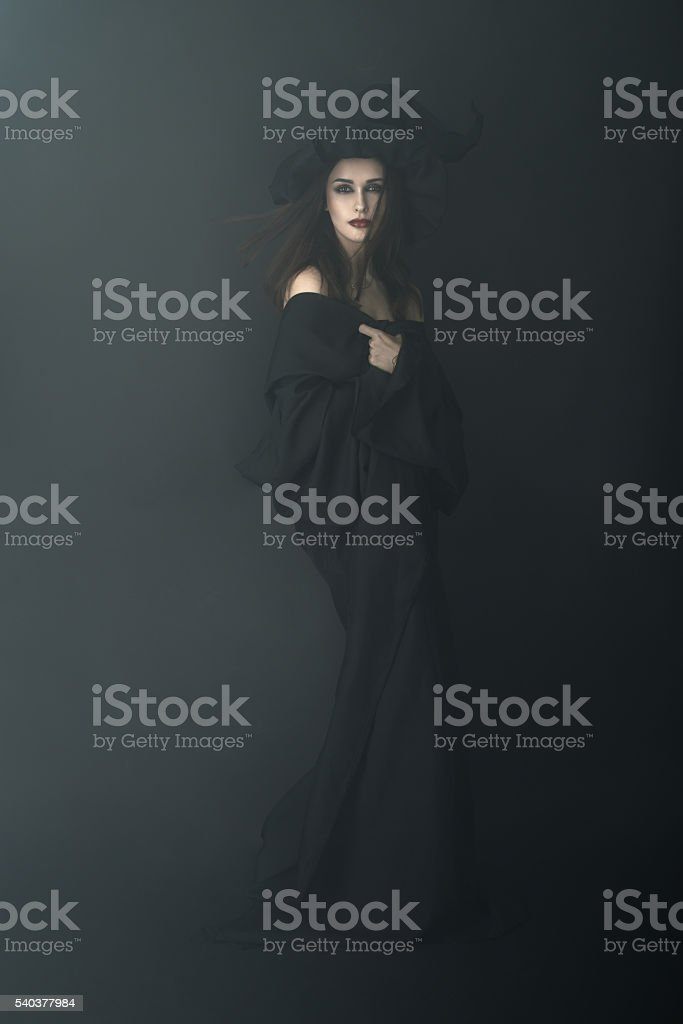 slender witch in a dark fog stock photo