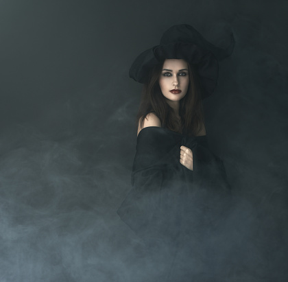 istock slender witch in a smoke on  black background 540378048