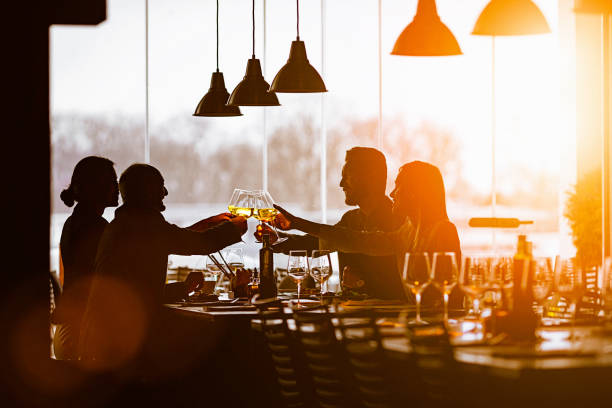 Slhouette of a Group of Friends Toasting During Lunch Time in a High-End Restaurant stock photo