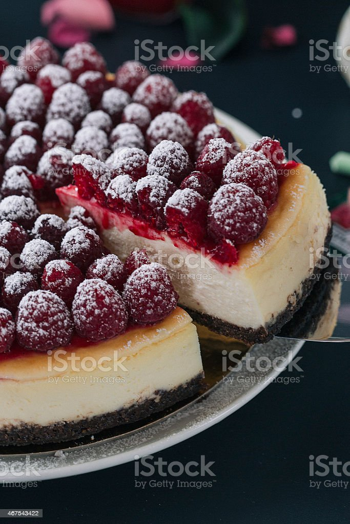 Slice being taken from a raspberry cheesecake stock photo