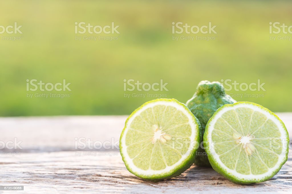 Slice green fresh Bergamot fruit on wooden table background royalty-free stock photo