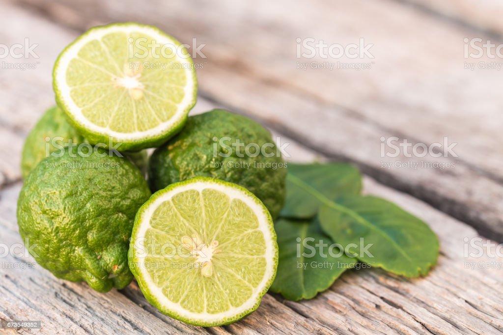 Slice green fresh Bergamot fruit on wooden table background royalty-free stock photo