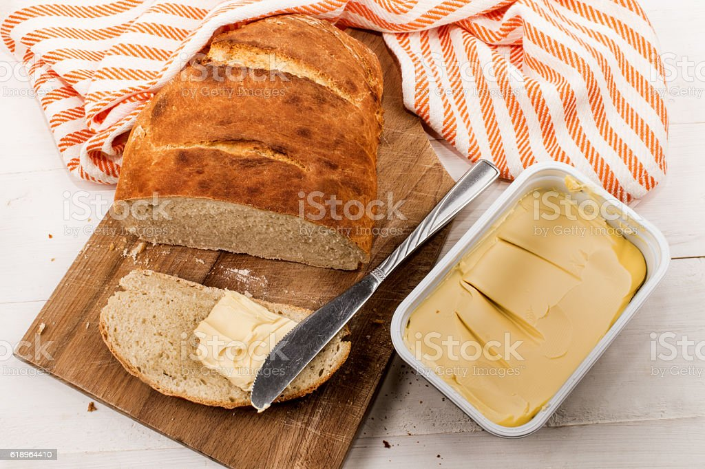 slice home baked bread with margarine on a cutting board stock photo