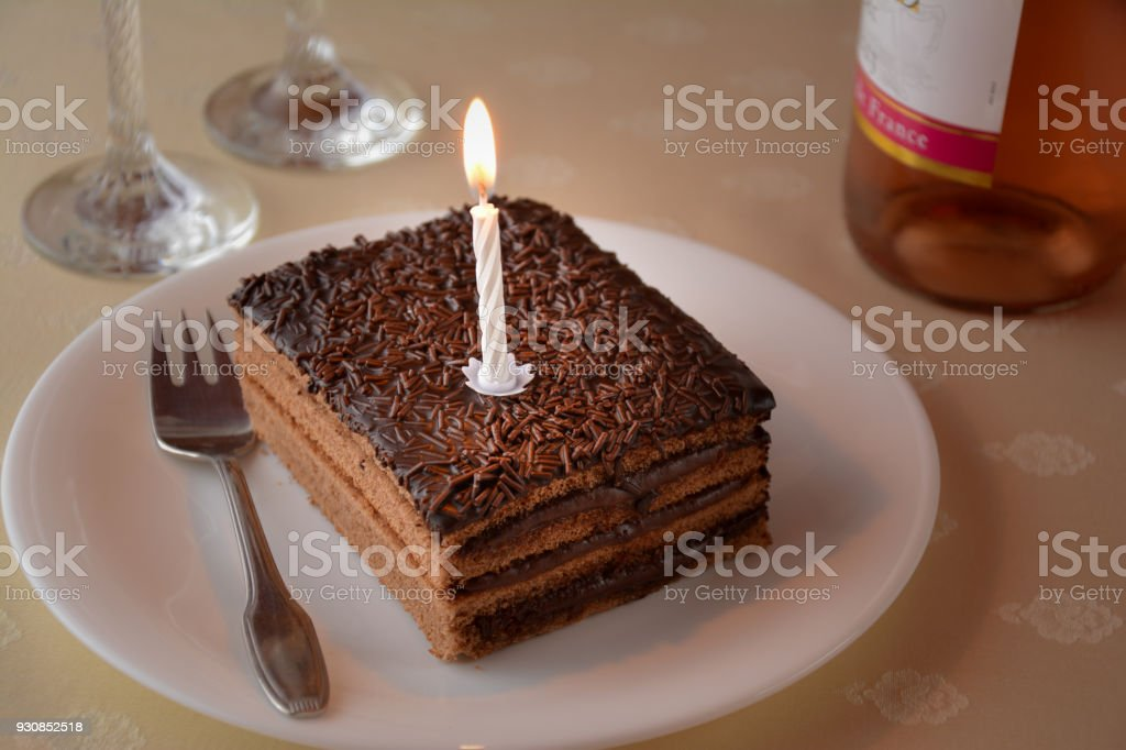 Slice Of A Chocolate Cake With One Candle And Two Glasses Bottle Wine