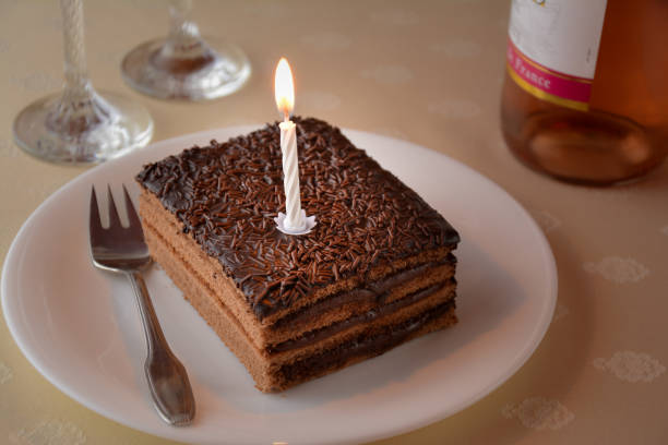 Slice Of A Chocolate Cake With One Candle And Two Glasses Bottle Wine Stock