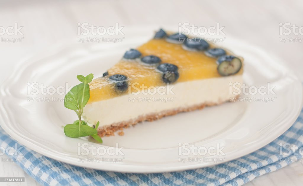 Slice of a Mango cheesecake with blueberries royalty-free stock photo