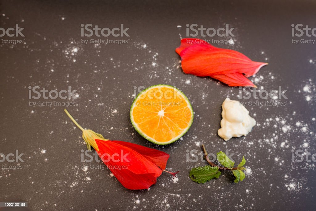 Slice Of An Orange Red Flowers Creme And Mint Isolated Over