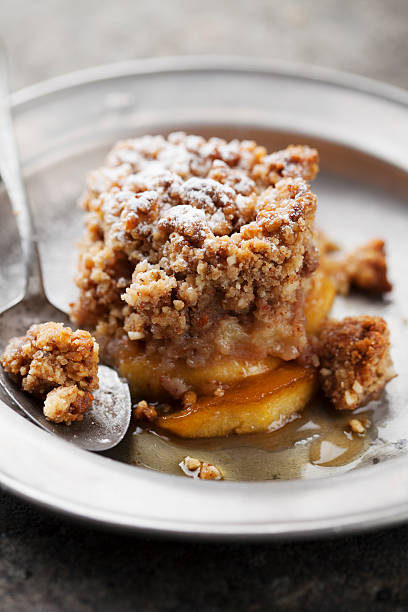 Slice of apple crumble on tin plate with spoon stock photo