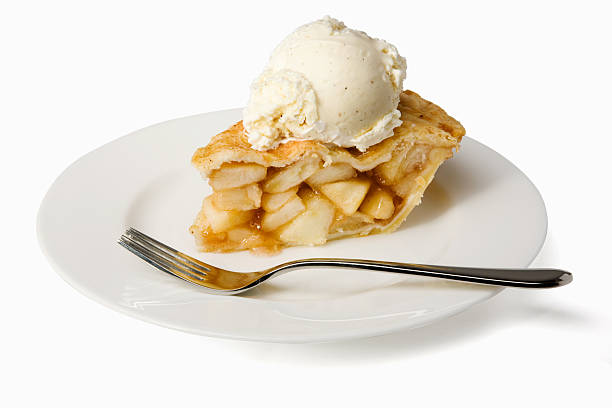 Slice of apple pie a la mode on a plate with a fork stock photo