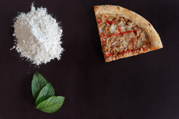 Slice of baked tuna pizza, pile of flour and green leaves on black background stock photo