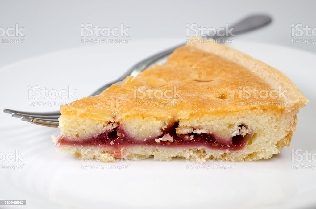Slice of bakewell tart on plate with fork stock photo