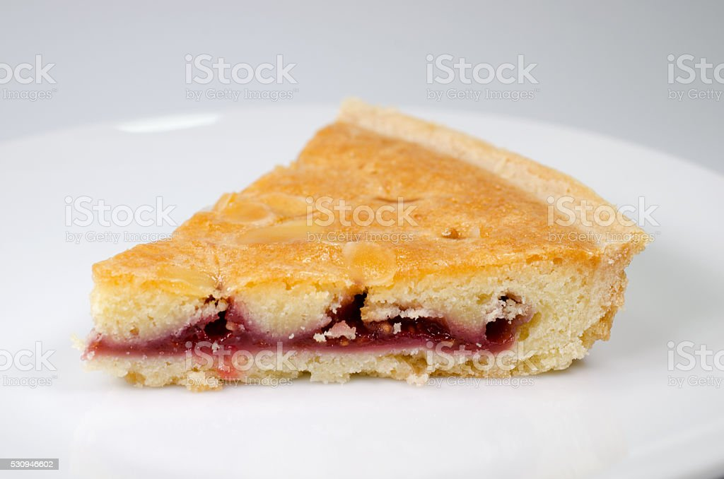 Slice of bakewell tart on white plate stock photo