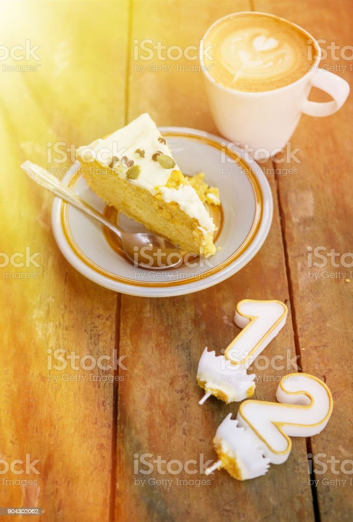Slice Of Birthday Cake Witn Candle Numbers One And Two With Cup