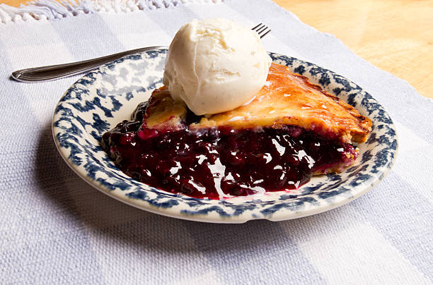 slice of blueberry pie with ice cream - blueberry pie stock photos and pictures