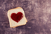 Slice of bread and jam in heart shape on rustic wooden table with copy space