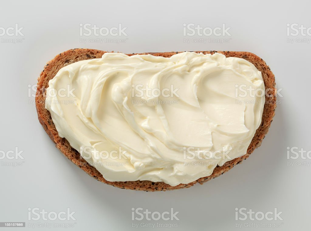 Slice of bread, spread with cheese against white background stock photo