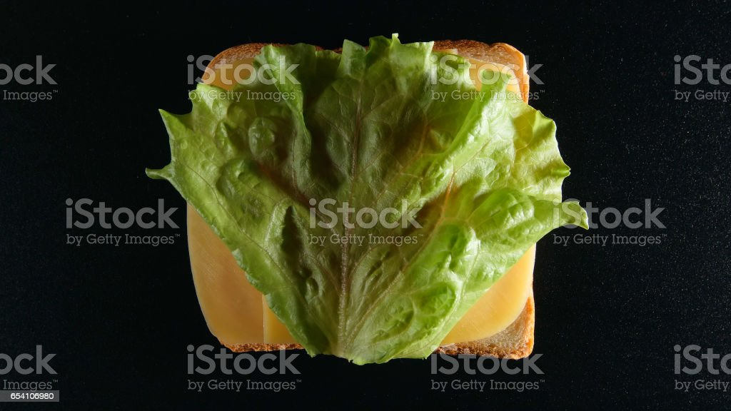 TOP VIEW: Slice of bread with a cheese and green leaf (lattuce) stock photo