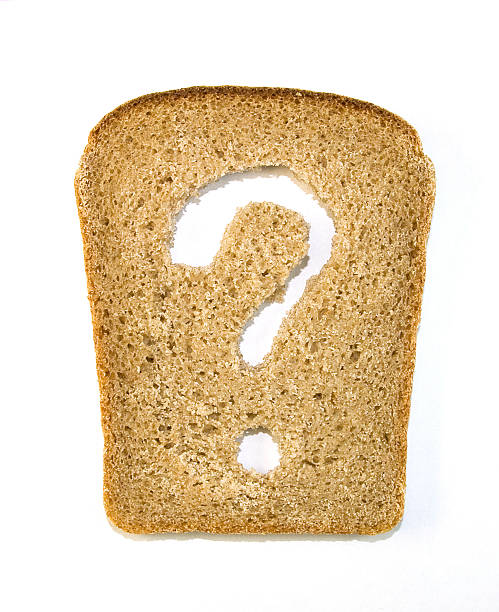 Slice of bread with a question mark cut out from it stock photo