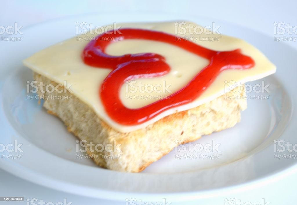 Slice of bread with cheese and heart shaped jam on top stock photo