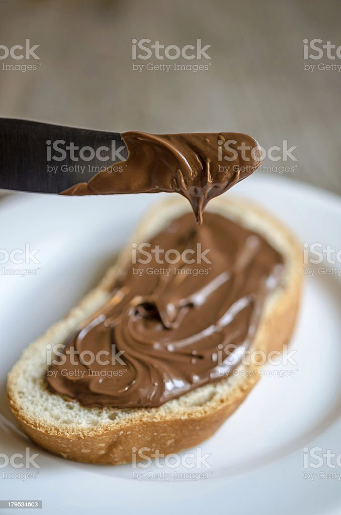 A slice of bread with chocolate spread and a knife royalty-free stock photo